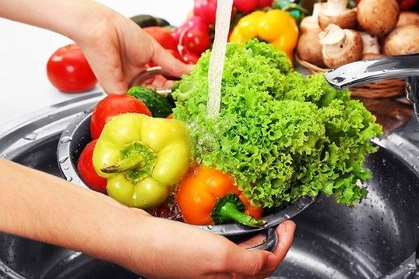 Девушка моет овощи перед едой.