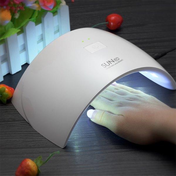Девушка сушит ногти в УФ-лампе.