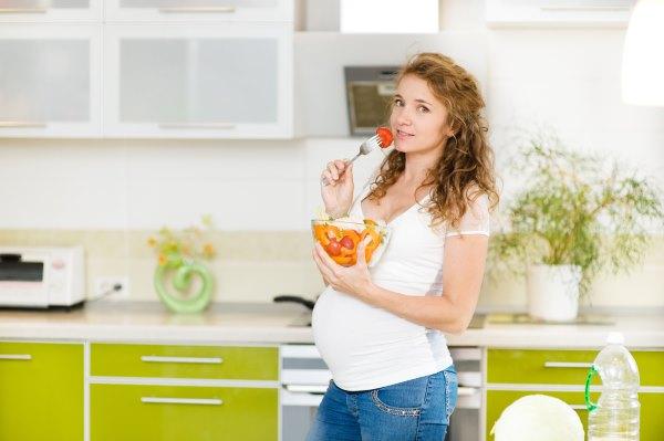 Беременная девушка ест.