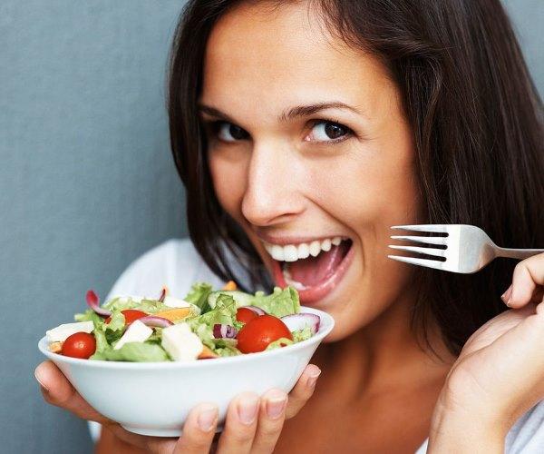 Девушка ест салат.
