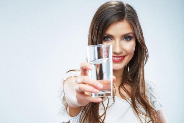Девушка протягивает стакан воды.