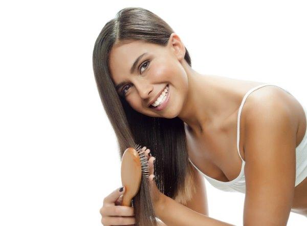Девушка расчесывает свои волосы..