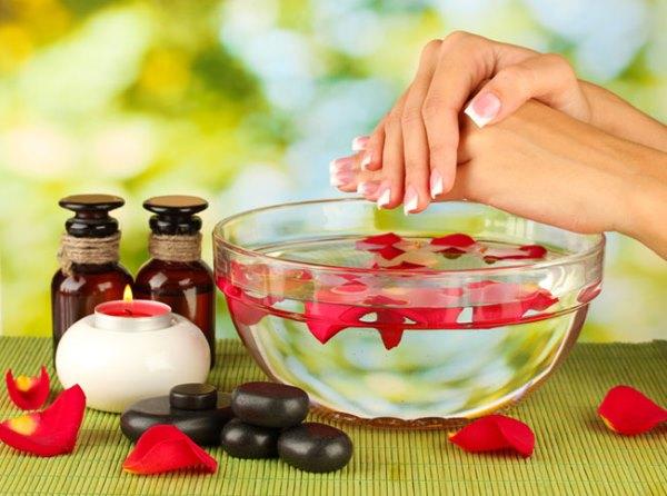 Девушка делает ванночку для рук с эфирными маслами.