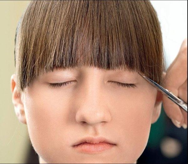 Девушке подстригают челку.