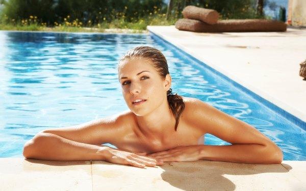 Девушка плавает в бассейне.