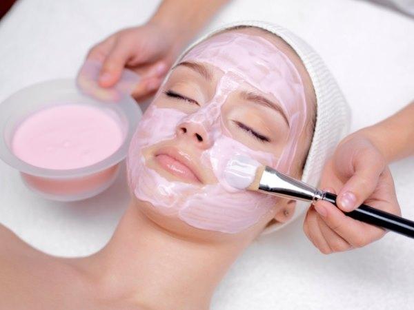Девушка делает себе маску с розовой глиной.