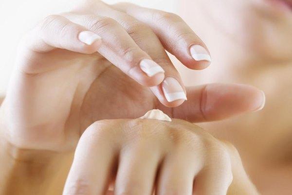 Девушка мажет руки кремом.