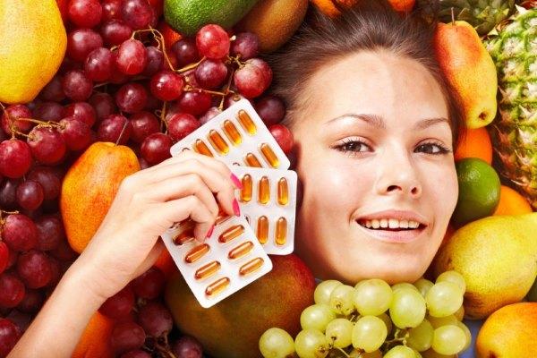 Девушка во фруктах держит витамины.