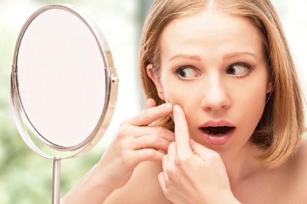 Девушка увидела пырщ на лице в зеркале.