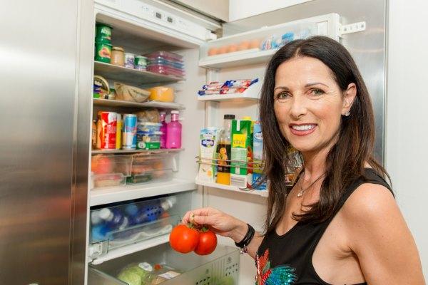 Девушка прячет еду в холодильник.