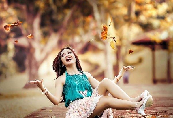 Счастливую девушка сидит на земле.