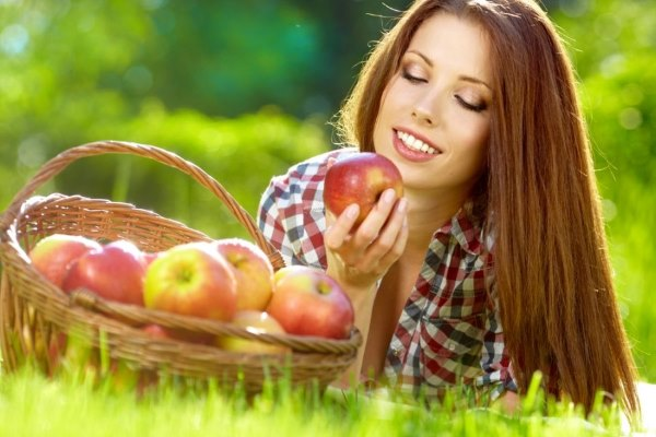 Девушка ест яблоко.
