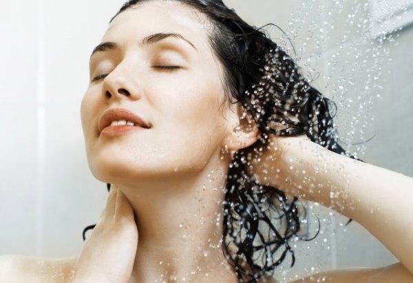 Девушка моет голову под душем.