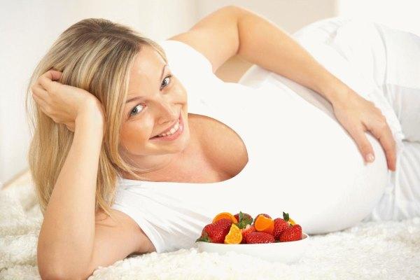 Беременная девушка ест овощи.