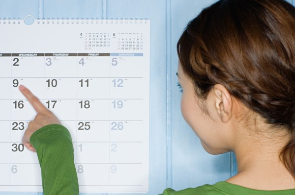 Девушка смотрит в календарь.