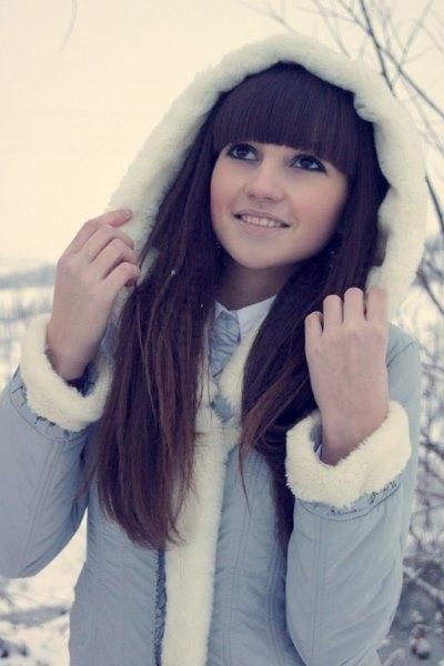 Девушка закрывает волосы зимой капюшоном.