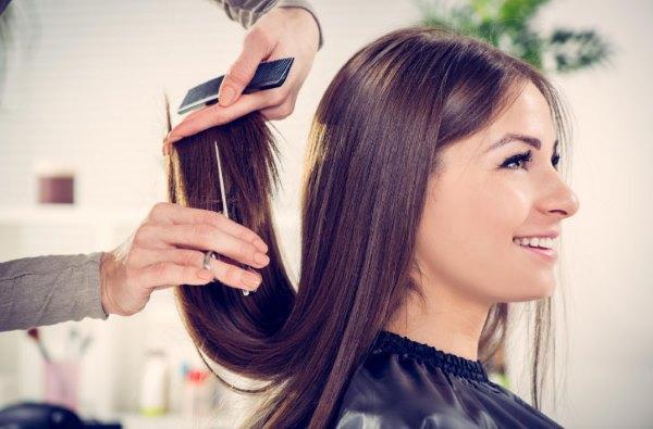 Девушке стригут волосы.
