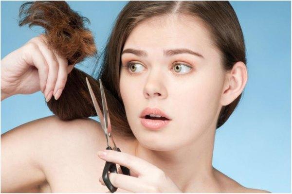 Девушка подстригает себе волосы.