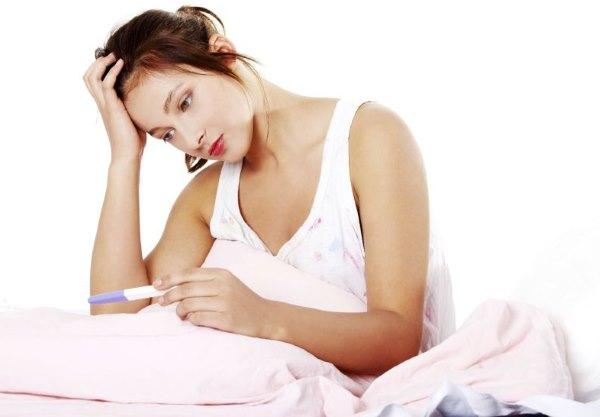 Девушка смотрит на тест для беременности.