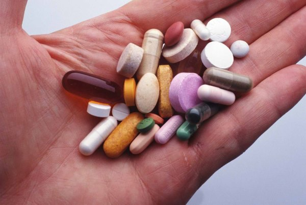 Разные таблетки в руке.
