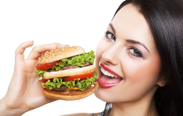 Девушка ест гамбургер.