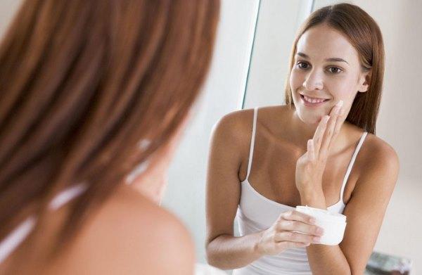 Девушка наносит мазь на лицо, глядя в зеркало.