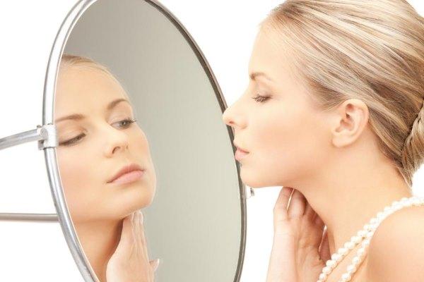Девушка рассматривает себя в зеркале.