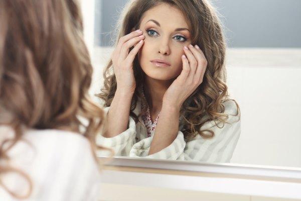 Девушка смотрит в зеркало и щупает свое лицо.