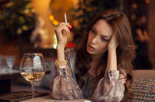 Девушка пьет алкоголь и курит.