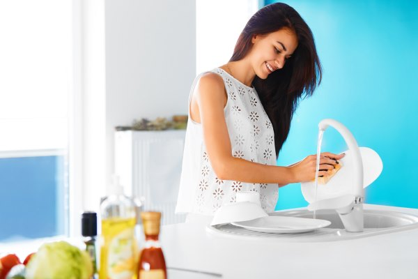 Девушка моет посуду.