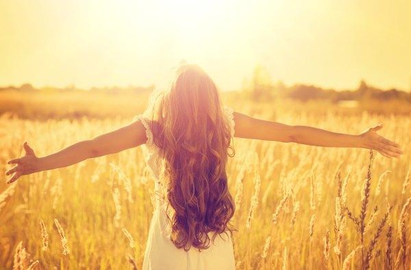 Девушка под солнцем в поле.
