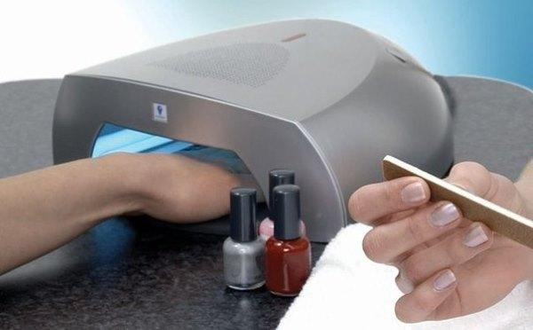 Девушка сушит ногти под лампой после маникюра.
