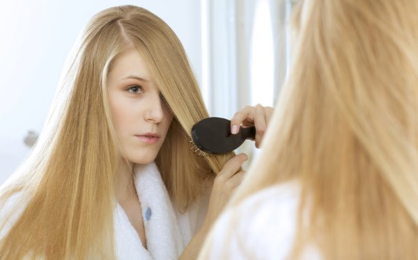 Девушка расчесывает свои длинные волосы.