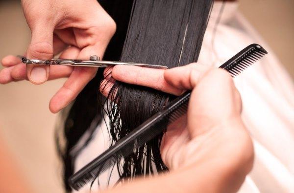 Девушке подстригают волосы.