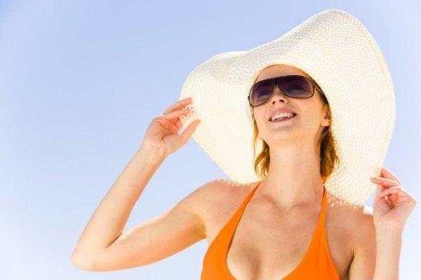 Надета шляпа и солнцезащитные очки