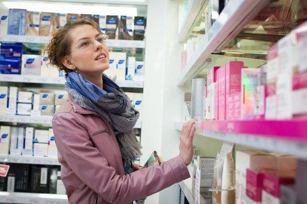 Девушка выбирает косметику в аптеке.