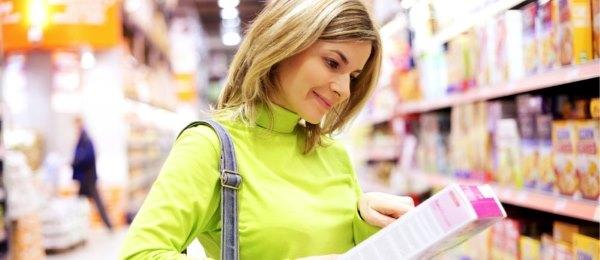 Девушка читает этикетку на косметике.