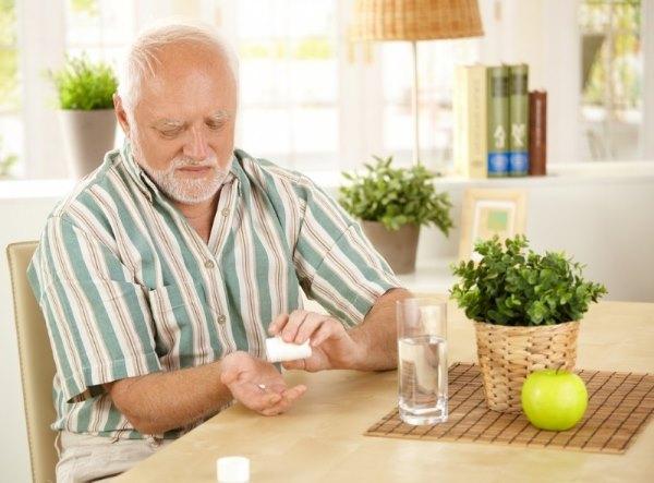 Пожило мужчина пьет витаминку.