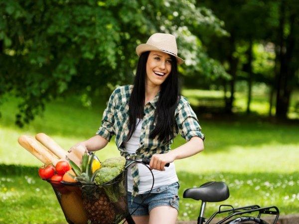 Девушка на велосипеде с овощами.