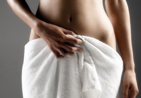 Девушка вытирает полотенцем паховую зону.