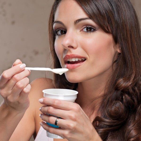 Девушка ест йогурт.