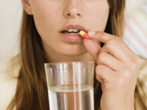 Девушка принимает таблетку.