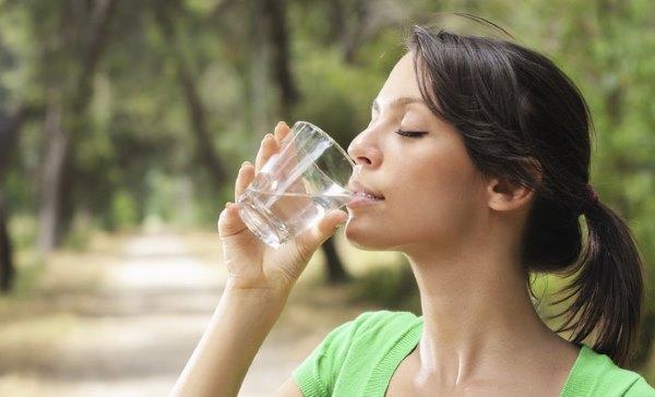 Девушка пьет воду.
