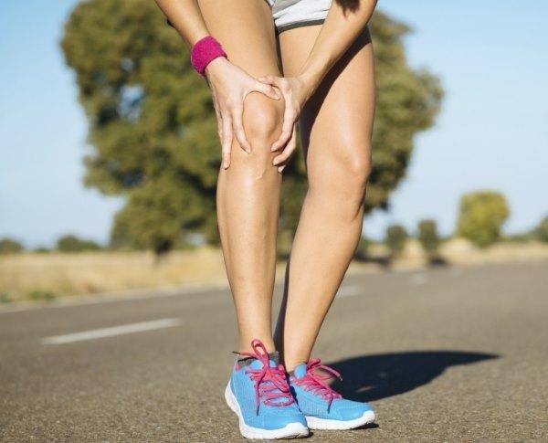 У девушки болит колено во время пробежки.
