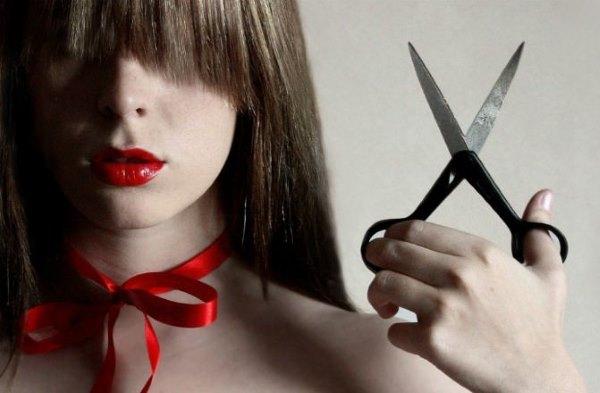 Девушка держит в руках ножницы.