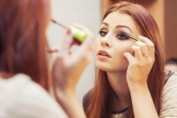 Девушка смотрит в зеркало и красит ресницы тушью.