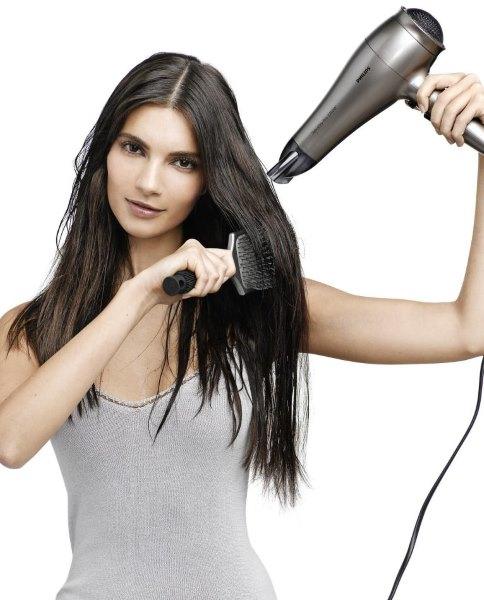 Девушка укладывает волосы феном.