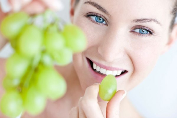 Девушка ест виноград.