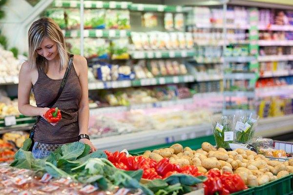 Девушка выбирает овощи в магазине.