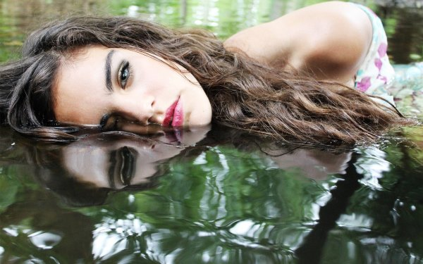 Девушка в воде с нарощеными ресницами.